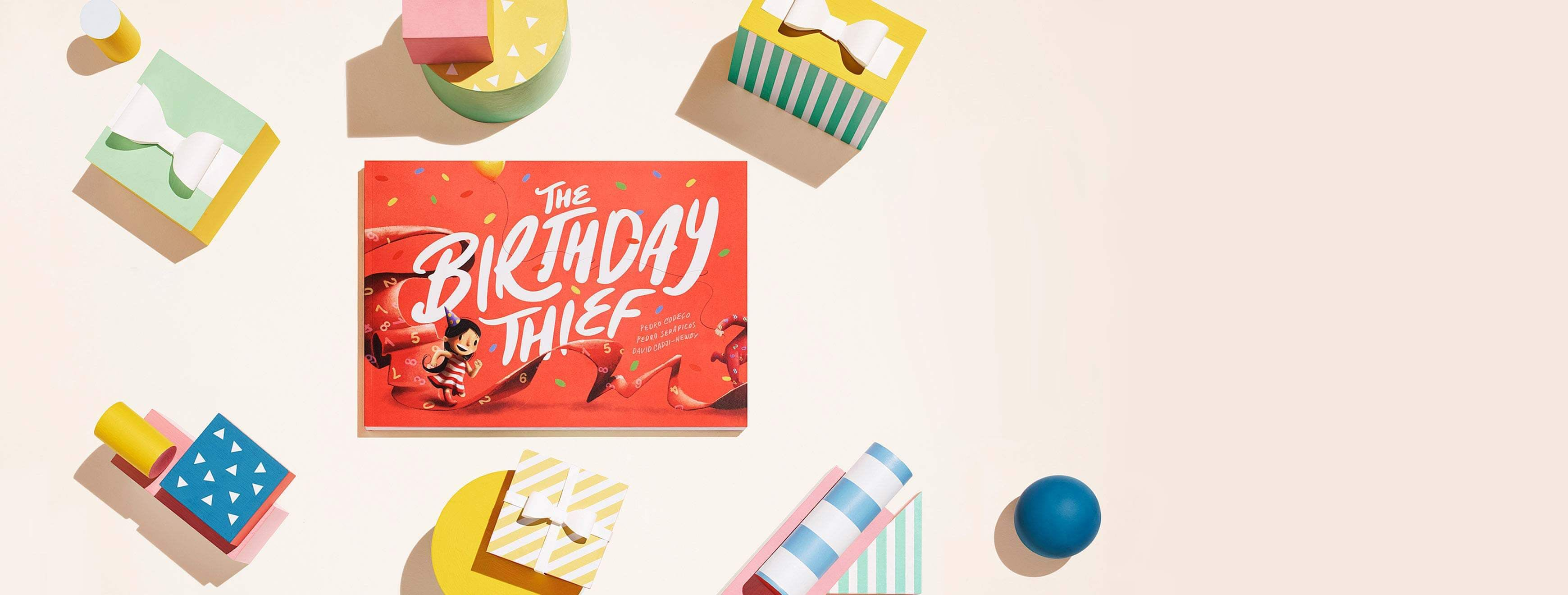 The Birthday Thief book laid on a cream backdrop with children blocks surrounding the book