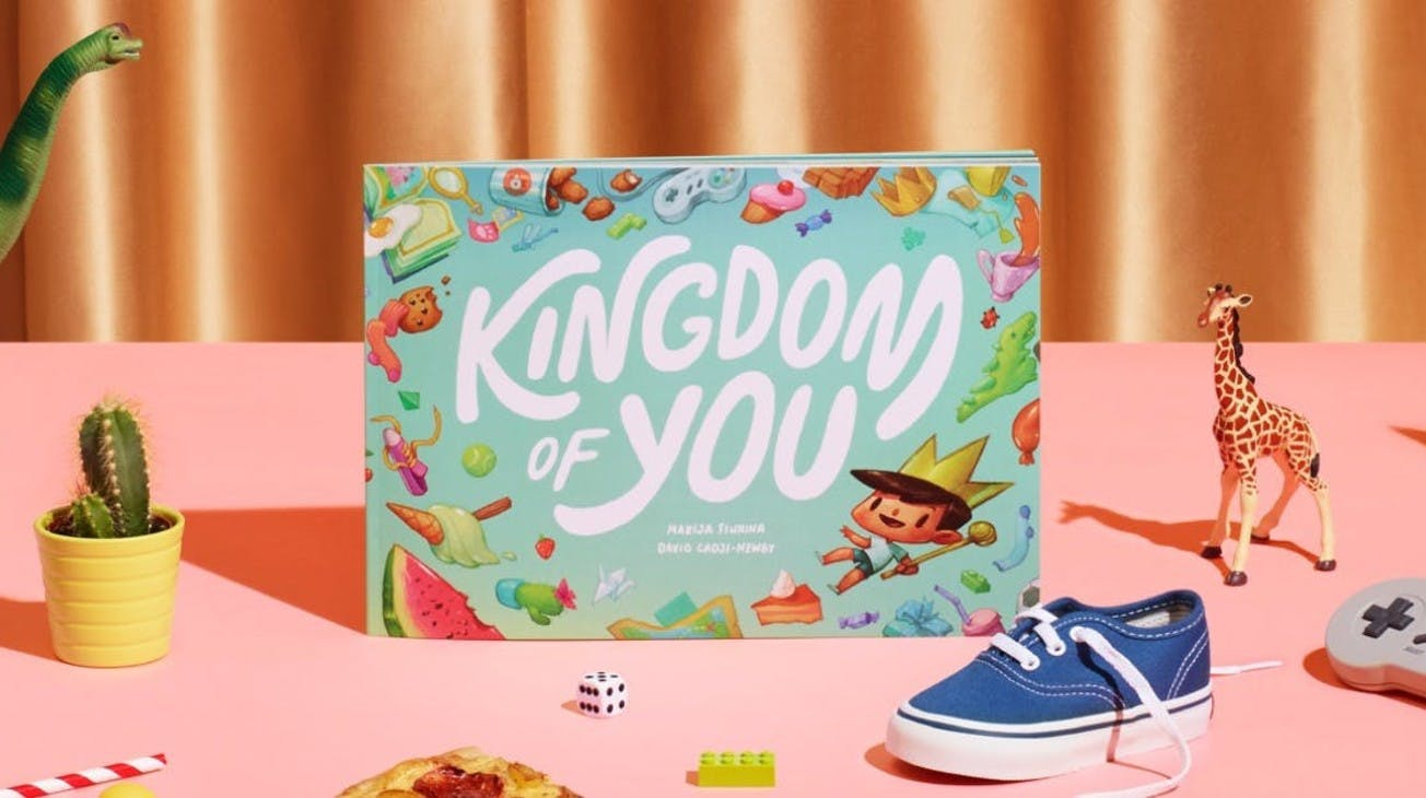 The Kingdom of you book sitting on a desk with different items surrounding it, such as cactus, lego, dice and pizza