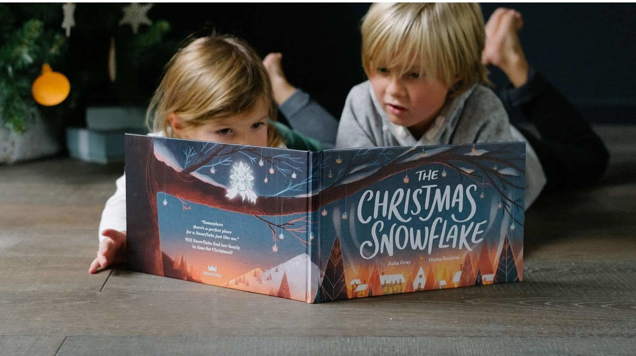 Brother and sister reading The Christmas Snowflake together