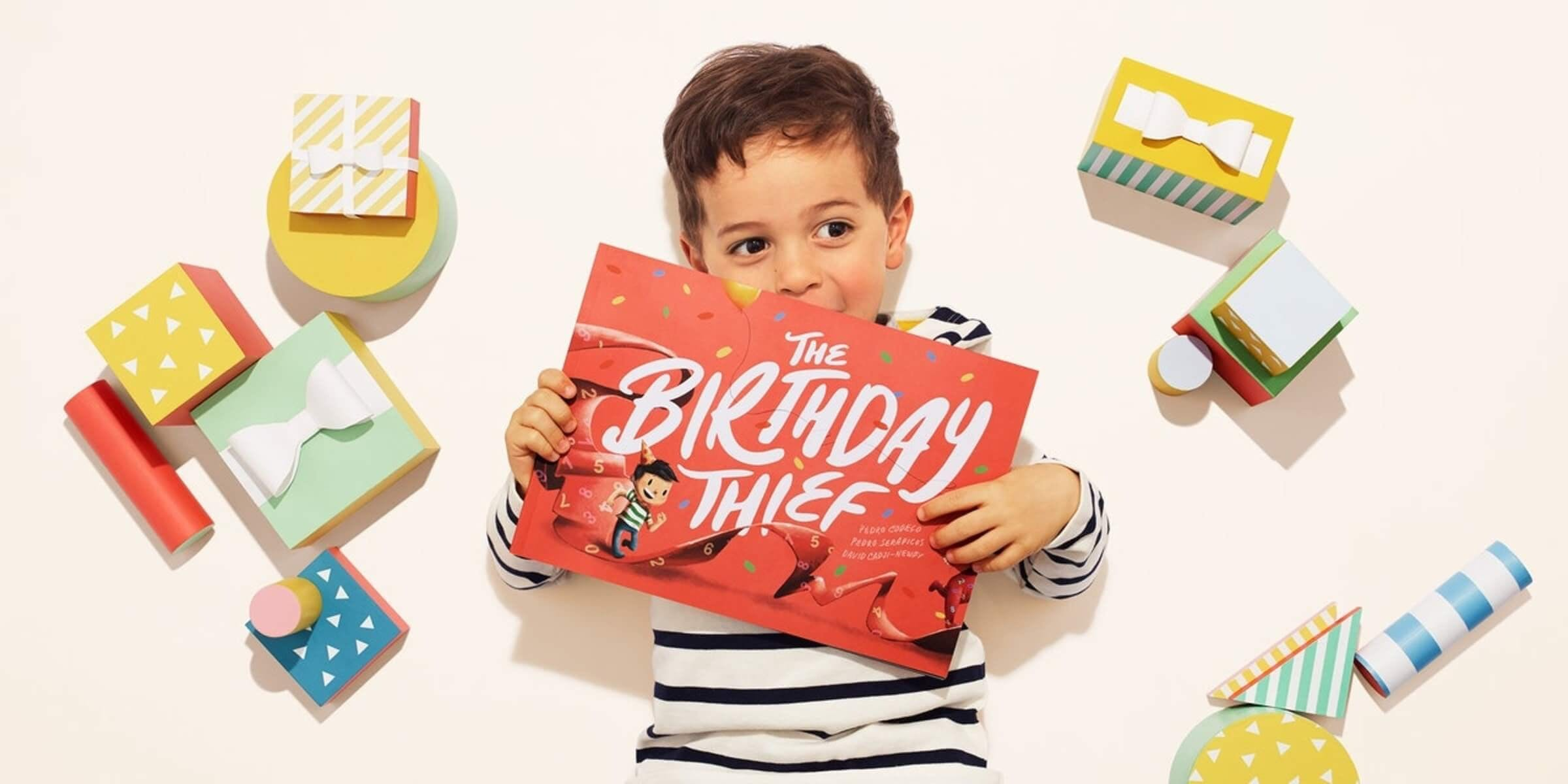 A little boy holding the Birthday Thief Book in the air with presents surrounding him