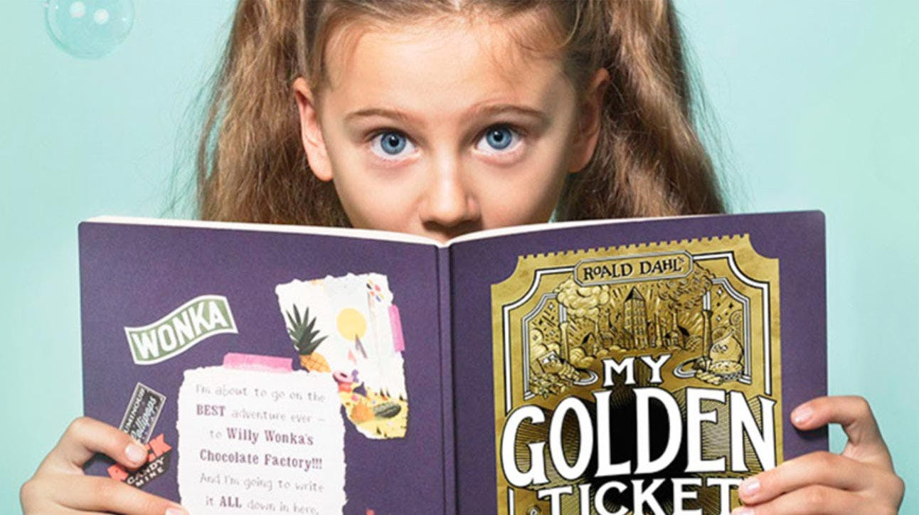 A little girl reading her personalised My Golden Ticket book