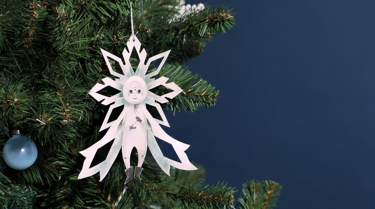 The Christmas Snowflake ornament hanging from a christmas tree