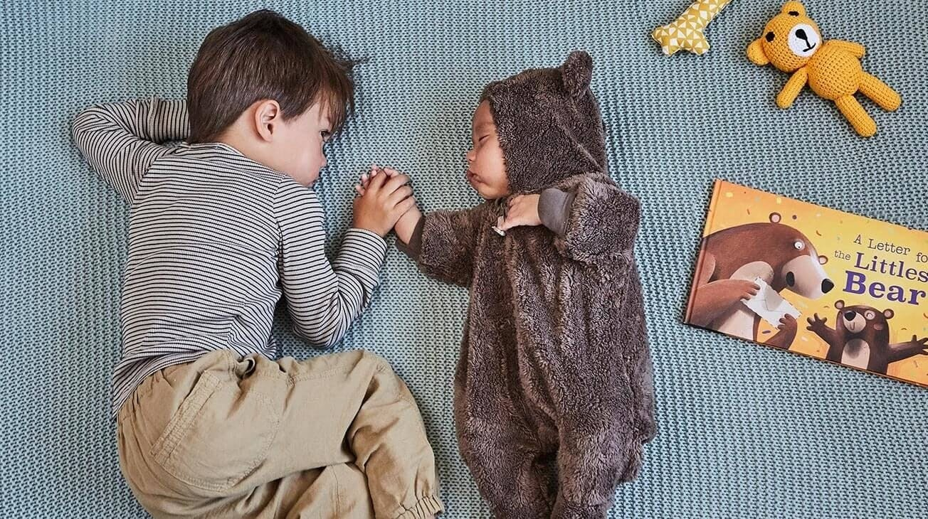 An image of  the older brother holding his little brother's hand, who is dressed in a little bear outfit