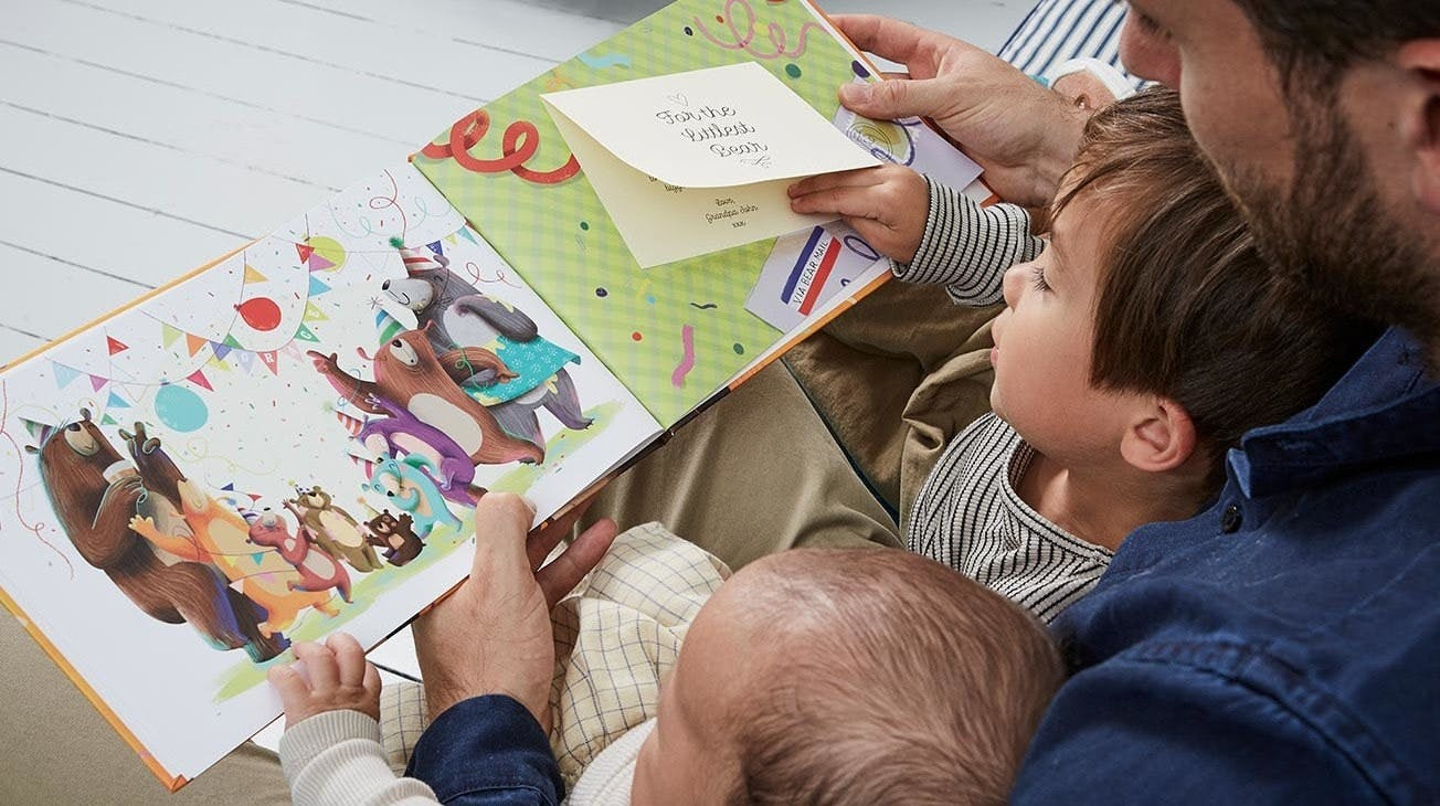 An image of the father with his two sons reading the Littlest Bear book to them