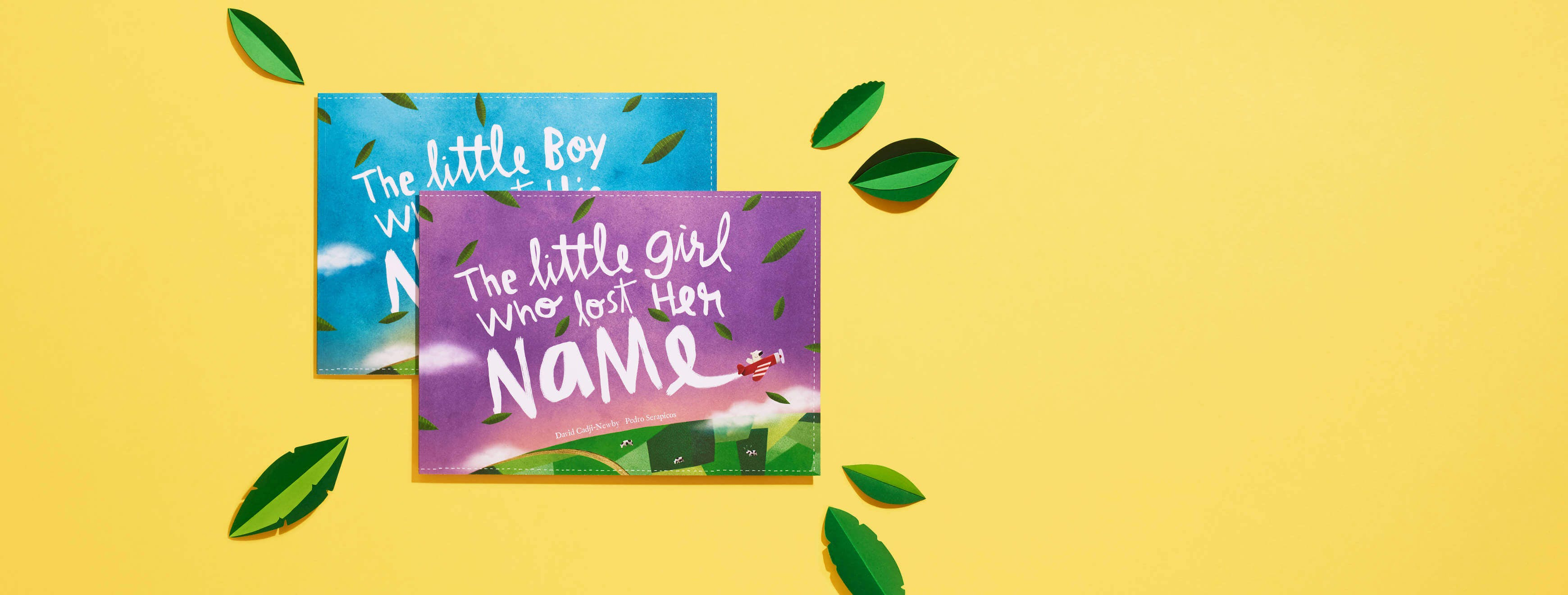 The little girl who lost her name and the little boy who lost his name laid on a yellow backdrop with several crafted leaves surrounding the book.